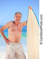 Mature man with his surfboard