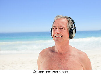 Retired man listening to some music on the beach