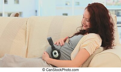 Pregnant woman with headphones on her belly in the living...