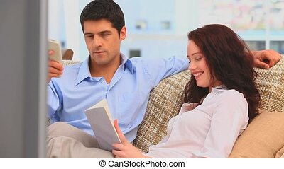 Man watching tv while his girlfriend is reading a bookat...