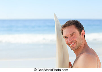 Handsome man with his surfboard