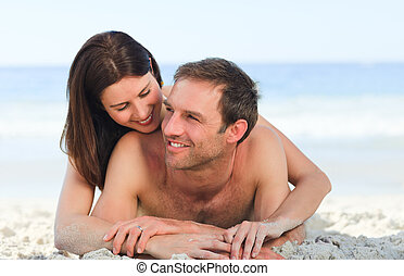 Couple lying down on the beach
