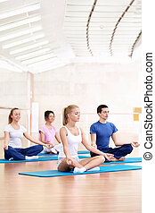 Yoga - Young people practice yoga in the fitness club