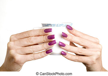 Female hands with long nails with manicure hold a cup