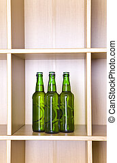 3 green glass bottles on a regiment