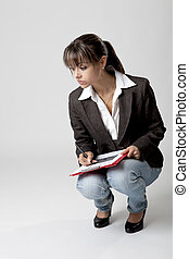 Beautiful woman takes notes - Business woman is crouching