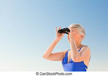 Senior woman bird watching at the beach