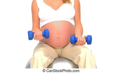 Pregnant woman doing exercises against a white background