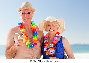 Senior couple drinking a cocktail on the beach
