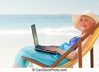 feliz, mujer, trabajando, ella, computador portatil, playa