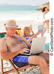 Man working on his laptop while his wife is reading at the...