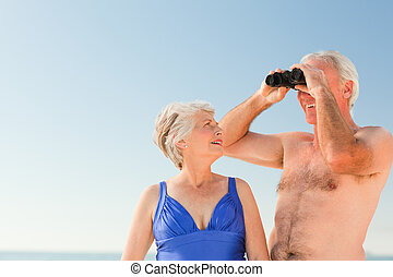 Elderly couple bird watching at the beach