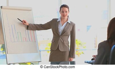Business woman using a blackboard to make a presentation in...