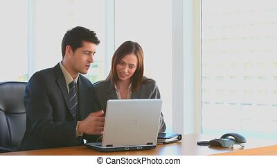Business people working on a laptop at a desk