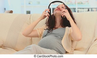 Woman putting headphone on her belly