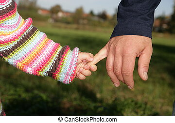 Hand holding - A parent holding the hand of its child while...