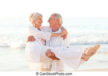 Man carrying his wife on the beach