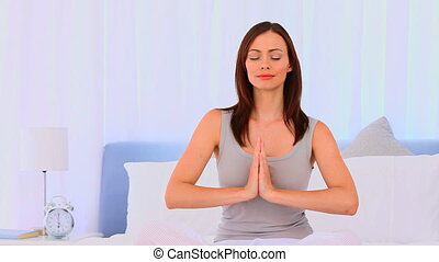 Peaceful woman practicing yoga on h