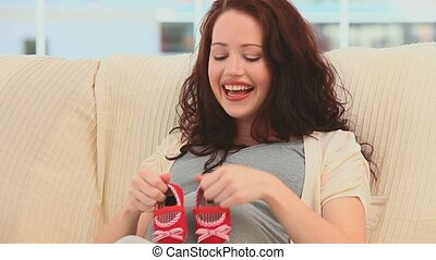 Pregnant woman playing with shoes - Pregnant woman playing...