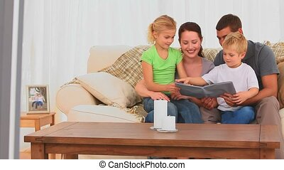 Cute family reading a book in the living room