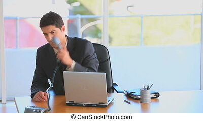 Businessman taking a phone call at his desk