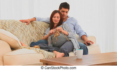 Pregnant woman knitting with her husband