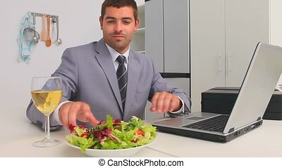 Businessman working on his laptop while he is eating