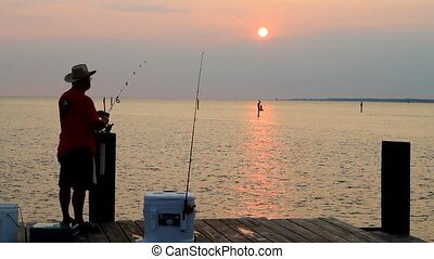 Sunset Fisherman - Senior adult man fishes from a pier as he...