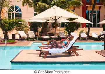 Girls sunbathing - Two women sunbathing on deckchairs by the...