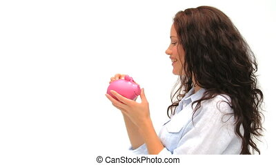 Woman and a piggybank - Woman putting her money in her piggy...