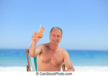 Senior man drinking a cocktail on the beach