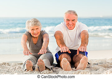 Couple doing their streches at the beach