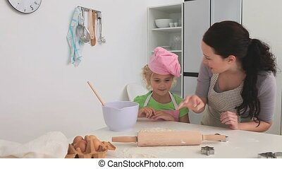 A mother cooking with her daughter