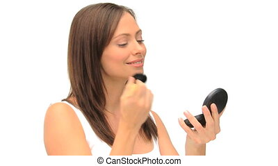 Coquette woman putting on make-up against a white background