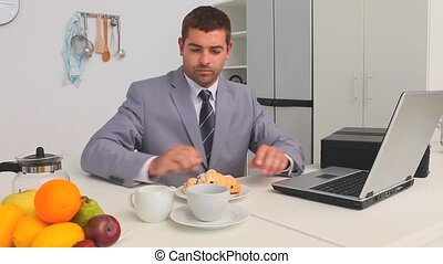 Businessman taking his breakfast while he is working on a...