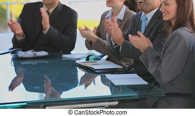 Business people applauding after a meeting at a desk