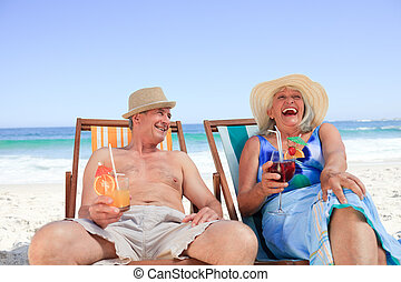 Mature couple sitting on deck chairs