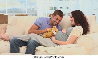 Lovely couple playing with a teddy bear on their couch