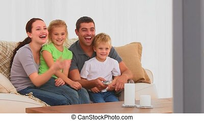 Family laughing in front of tv in the living room