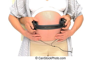 Man putting headphone on the belly of his pregnant wife
