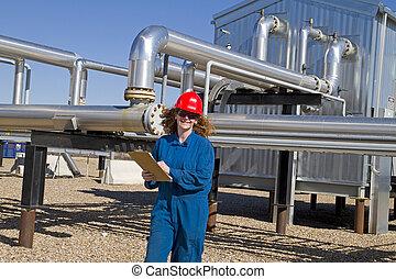 female gas field operator inspects compressor site - female...
