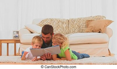 A father reading a book with his children in the living room