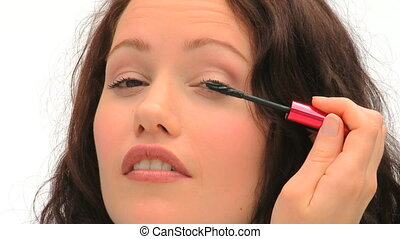 Brown-haired woman putting make-up on her eyelashes