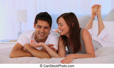 Couple lying down on their bed