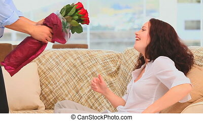 Man bringing a bunch of flowers to his wife in the living...