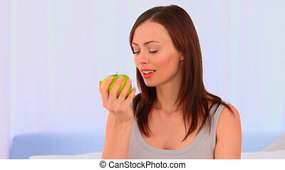 Relaxed woman eating an apple