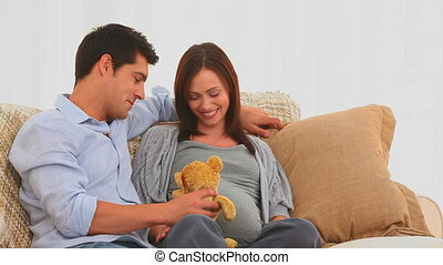 Pretty couple playing with a teddy