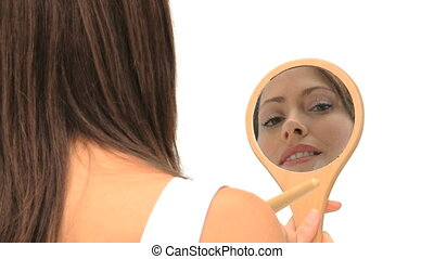 Nice brunette putting on make-up with a mirror and a brush
