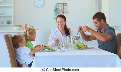 Family eating together in the kitch