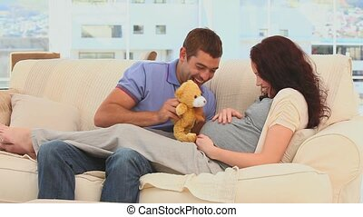 Future parents playing with a teddy bear in the living room